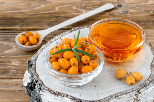자작 나무 그루터기에 작은 유리 접시에 바다 갈매 나무 열매와 기름 - 씨벅턴 뉴스 사진 이미지