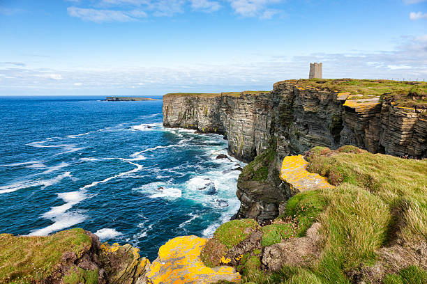 Sea Cliffs at Marwick Head, Orkney The Kitchner Memorial tower on the cliffs at Marwick Head on the west coast of the Orkney Mainland in the Orkney Islands off the northeast of Scotland. The high cliffs of Marwick Head, around 300 feet or 100 metres in height, are an important breeding ground for sea birds. The Kitchner Memorial tower was unveiled in 1926 to commemorate Lord Kitchner, British Minister of War, and the crew of HMS Hampshire who died here in 1916 during the First World War when the ship hit a mine. theasis stock pictures, royalty-free photos & images