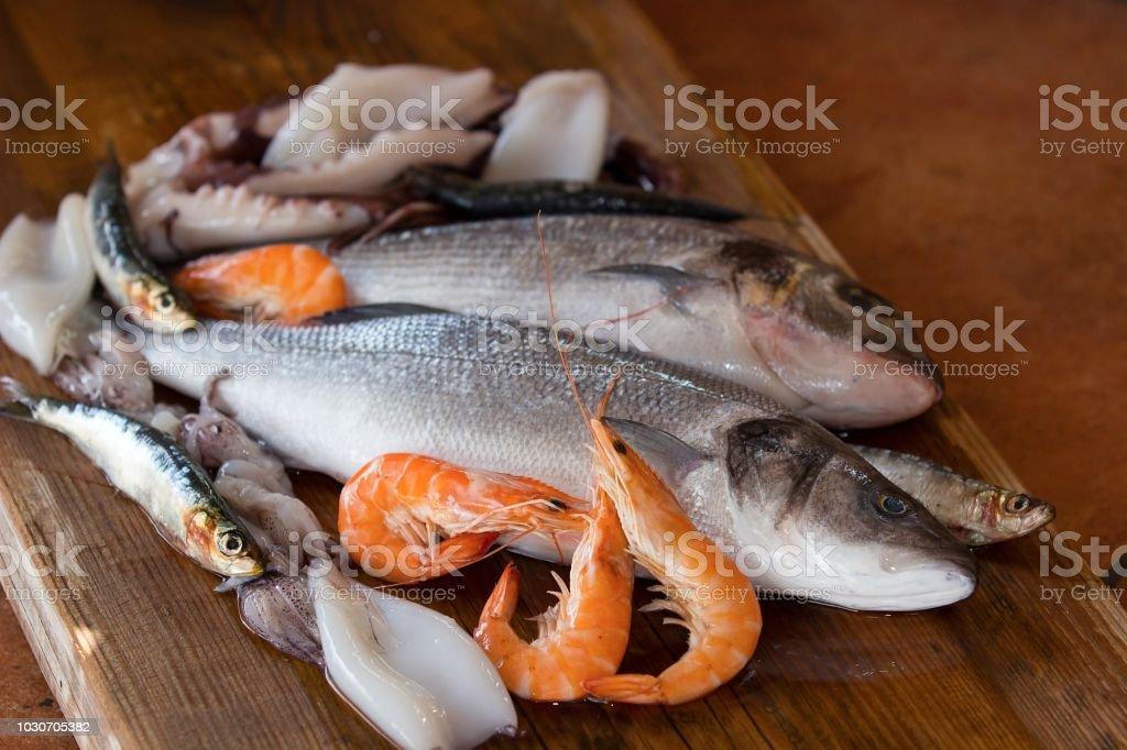 sea fish, prawns and calamari on wooden mat stock photo