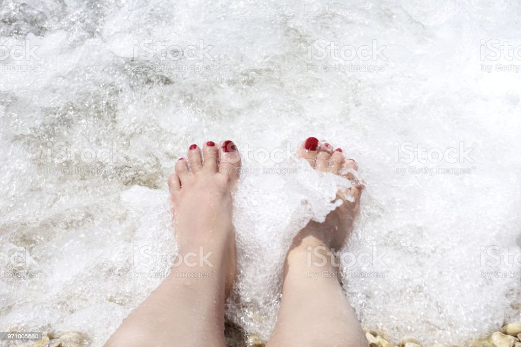 Sea foam and woman legs on it. Summer vacation and relaxation concept stock photo