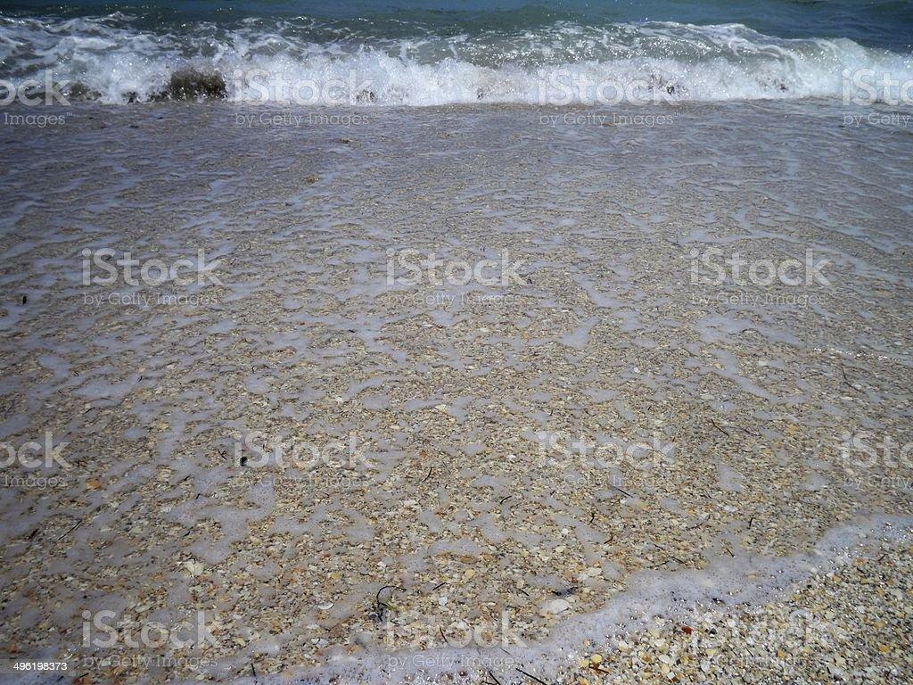 Sea Foam over the sand and shore stock photo