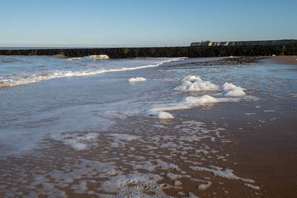 Sea foam washing up on the beach in Kent, UK stock photo