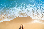 Sea foam, waves and naked feet on a sand beach. Holidays, relax, summer background