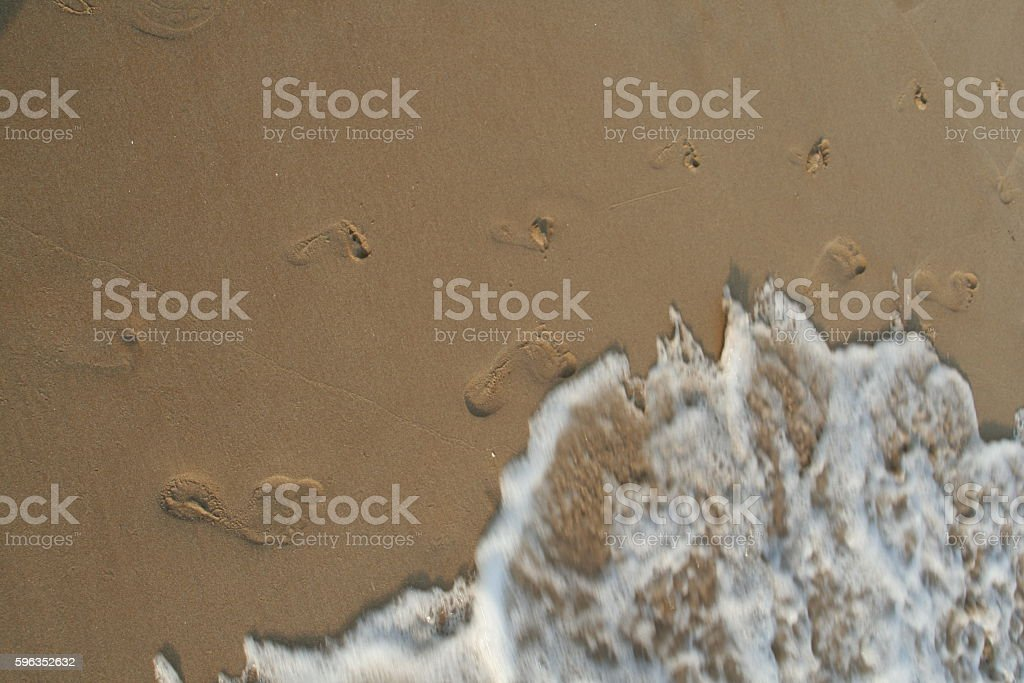 Sea foam waves on the beach washes footprints of adult royalty-free stock photo