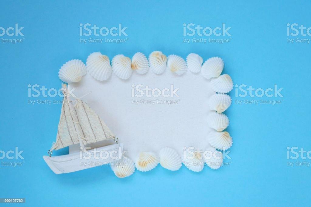 Sea frame.white styrelse med vita snäckskal och en båt på en ljusblå bakgrund. ovanifrån, kopiera utrymme. Sommartid.Sommarsäsongen - Royaltyfri Antända Bildbanksbilder