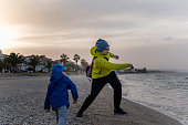 Father and son throwing stones in the sea