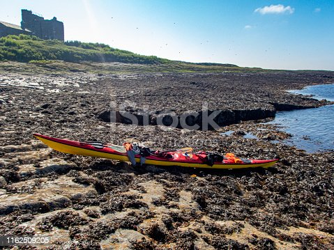 Sea Kayak on the Farne Islands with the shoreline of other islands in the background.This is on Inner farne with the Chapel of St Cuthbert in the background.