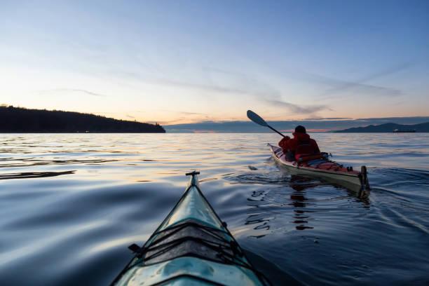 kayak de mar durante la puesta de sol - kayak fotografías e imágenes de stock