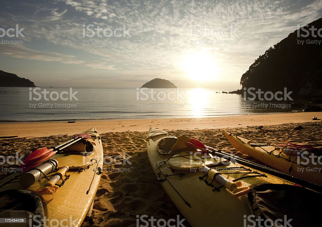 Sea kayaks on beach at dawn, Abel Tasman, New Zealand stock photo