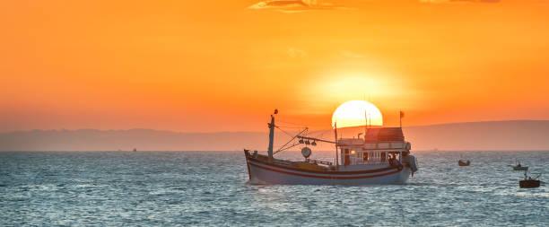 Meereslandschaft bei Sonnenuntergang, wenn Fischerboote aufs Meer, um Fische zu ernten, den Tag beenden. – Foto