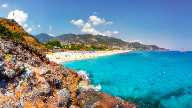 Sea landscape of the Mediterranean on clear sunny day. Sandy beach, rocks, blue sky, mountains and sea. Paradise Bay in Alanya. Tropical resort for summer holidays. coastline of sea resort beach. stock photo