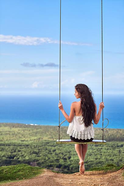 sea landscape with a girl on swing - mujeres dominicanas fotografías e imágenes de stock