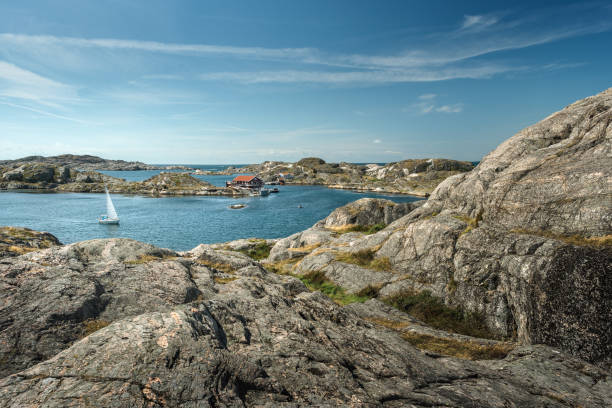 Sea landscape with sailboat and rocky coastline on the South of Sweden. Southern coastline of Sweden with view at sailing-ship and rocky islands. stock photo