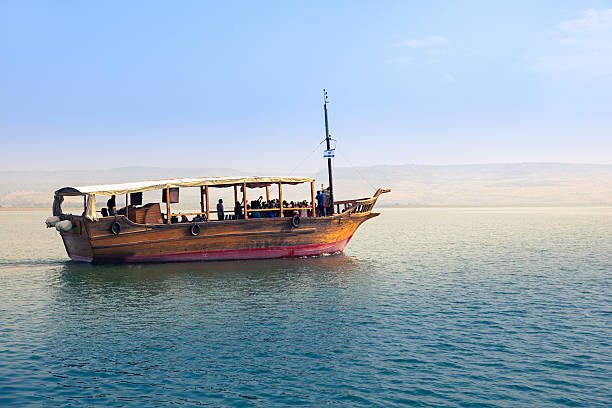 Sea of Galilee Sea of Galilee, Israel, Boat in sunset, Golan Heights in the background historical palestine stock pictures, royalty-free photos & images