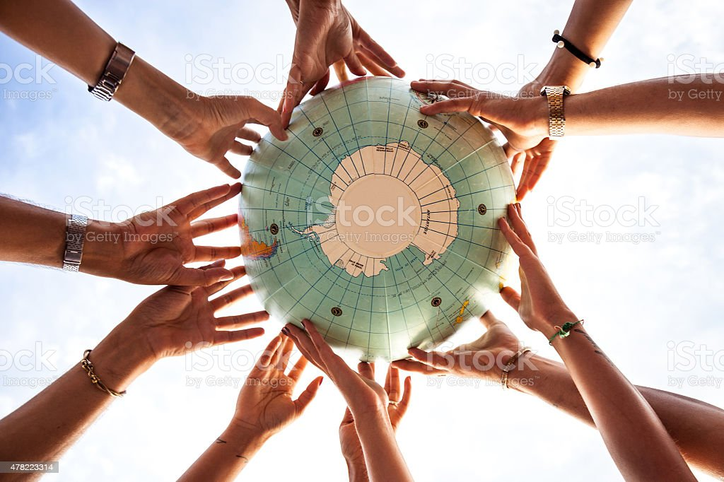 Sea of hands holding an earth globe stock photo
