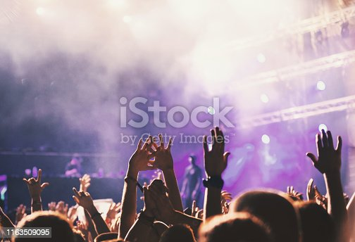 Rear view of group of unrecognizable people with their hands raised at music festival. Location: Music festival