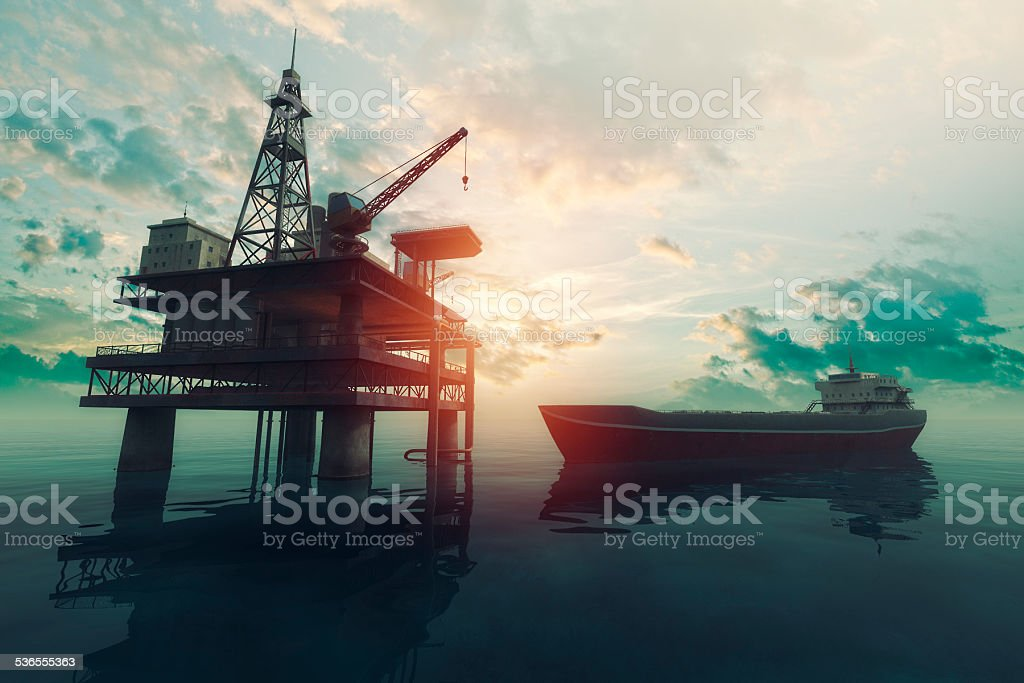 Sea oil rig with approaching tanker ship at sunset stock photo