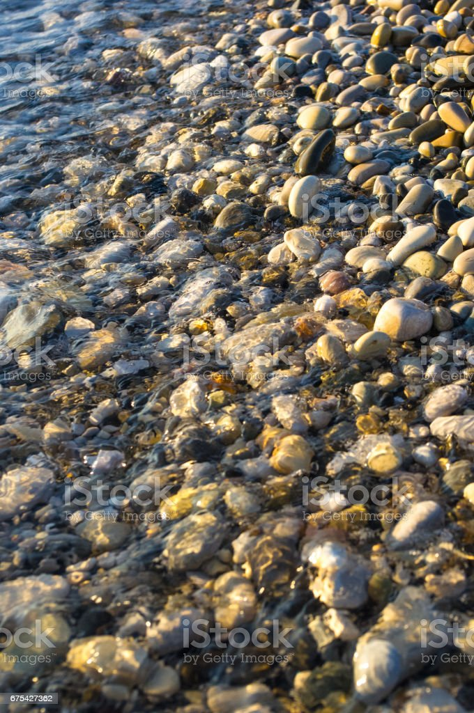 sea pebble beach with multicoloured stones, waves with foam photo libre de droits