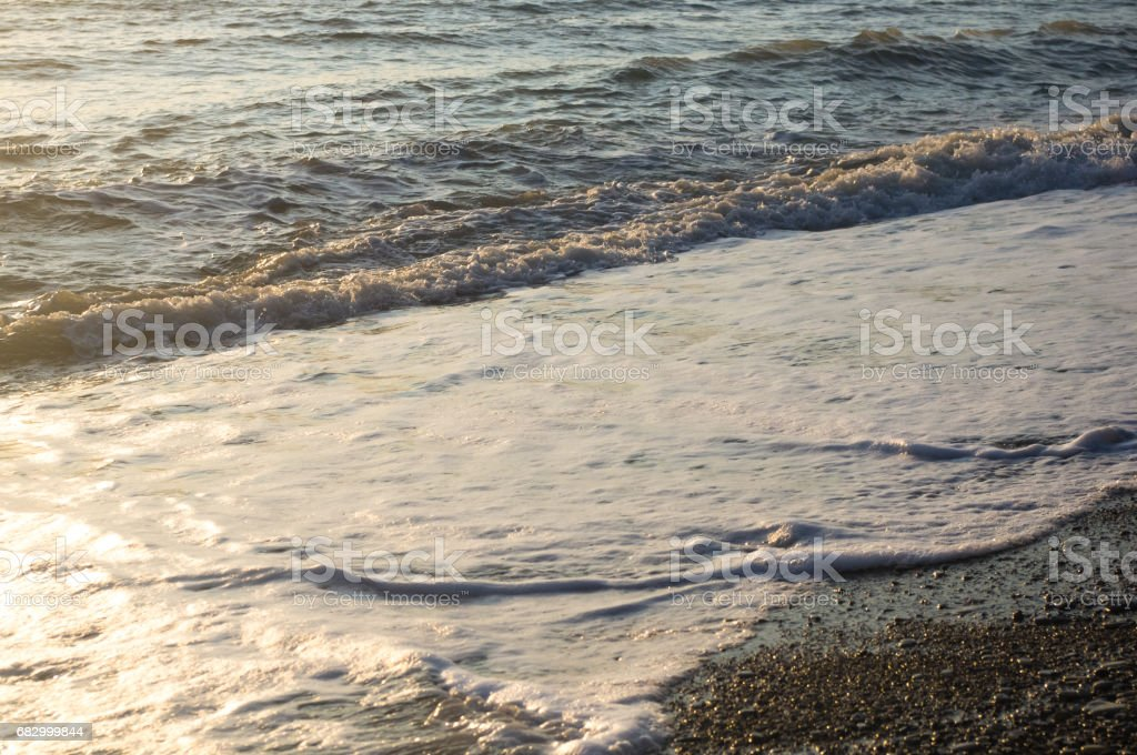 sea pebble beach with multicoloured stones, waves with foam royalty-free stock photo