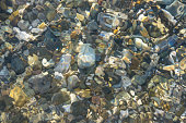 sea pebble beach with multicoloured stones, transparent waves with foam, on a warm summer day