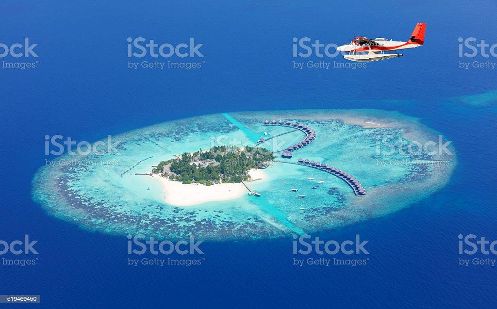 Sea plane flying above Maldives islands stock photo