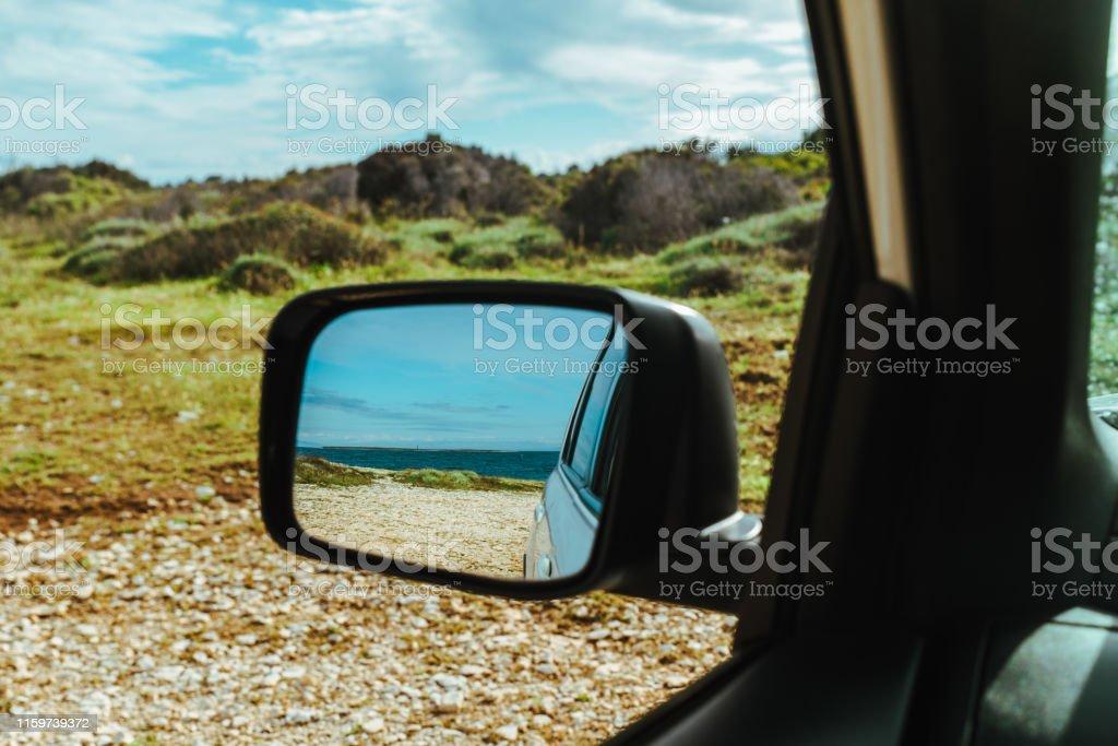 sea reflection in car rear mirror. road trip. summer vacation