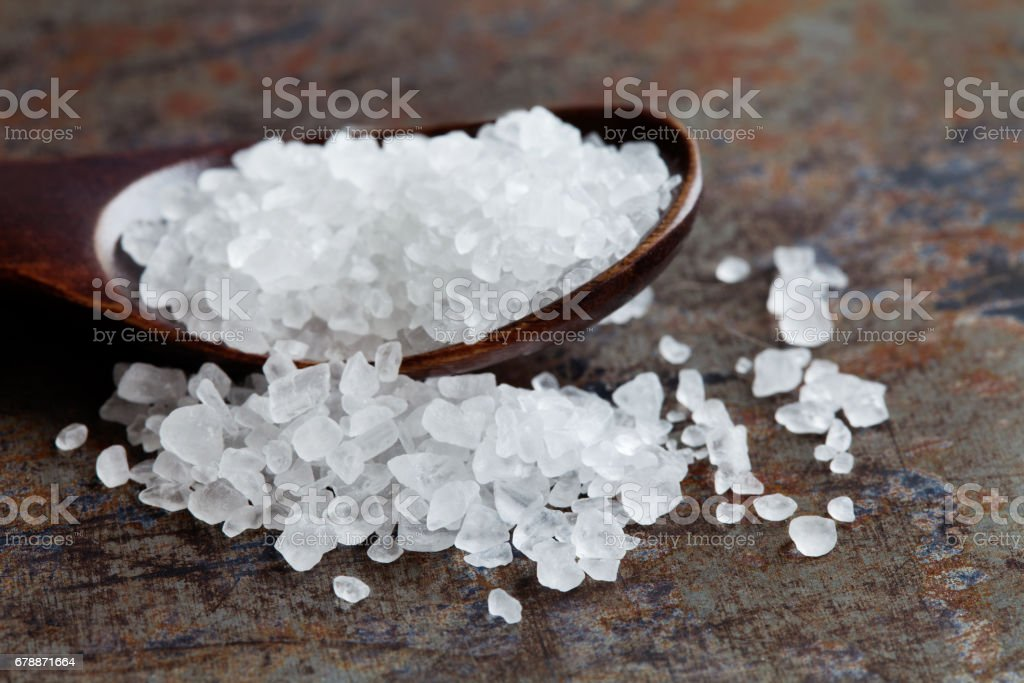Sea salt condiment macro view. Natural mineral flavoring food preservative, Saline sodium chloride white crystal in wooden spoon, aged background. Shallow depth field stock photo