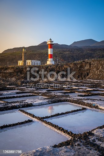 Coast with lighthouse and sea salt evaporation ponds at sunrise