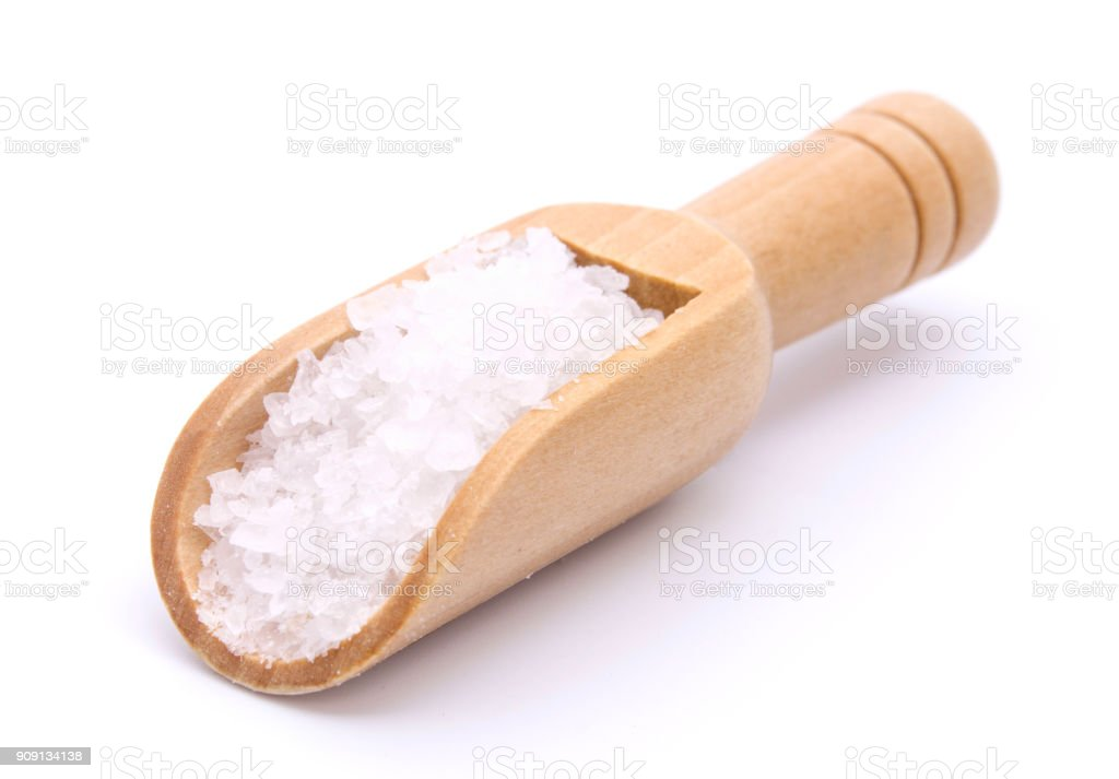 Sea salt in wooden scoop isolated on white background stock photo