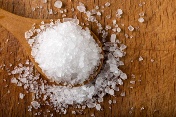 Sea salt in wooden spoon over wood stock photo