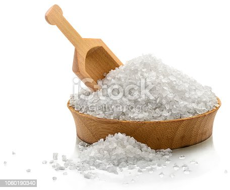 Bowl of coarse salt with a serving scoop.  Isolated on white.