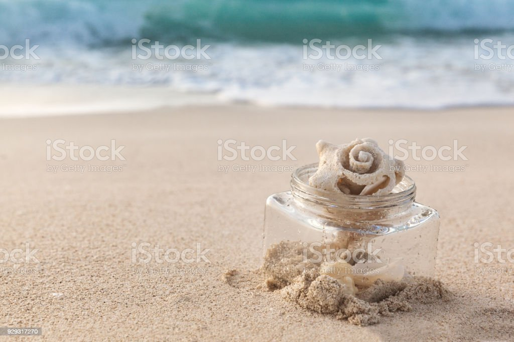 Sea Shell In A Glass Jar On The Beach With Sand And Ocean stock photo