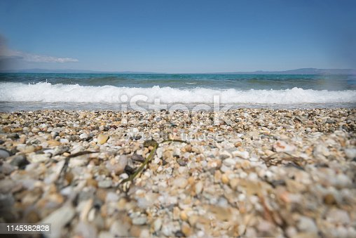 A selective focus low shot of beach pebbles and waves in the background