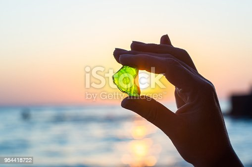 istock sea smoothed green glass in hand 954418722