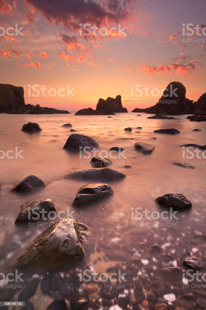Sea stacks near Ballintoy Harbour in Northern Ireland at sunset stock photo