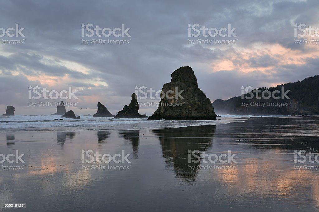 sea stacks reflected on beach at low tide stock photo