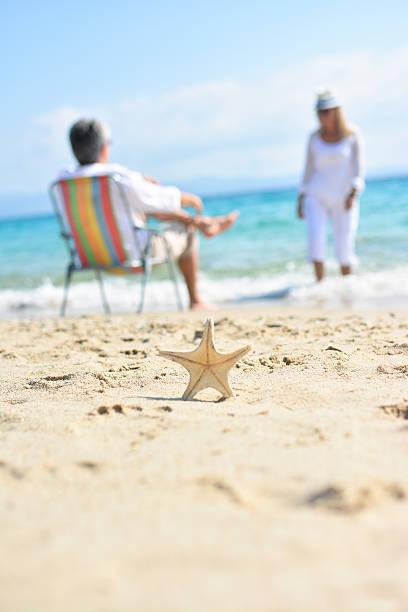 Estrela do mar na areia com casal no backgraund - foto de acervo