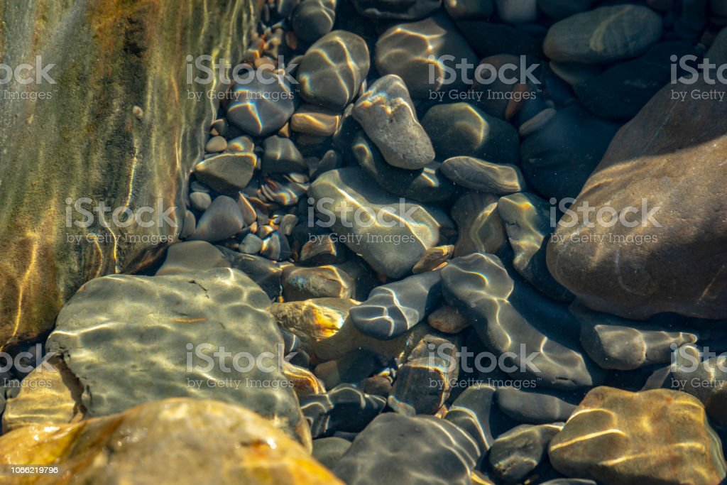 Sea stones and rocks of different sizes and texsture of black, gray and brown under the water on the Black Sea coast as nature bacground. stock photo