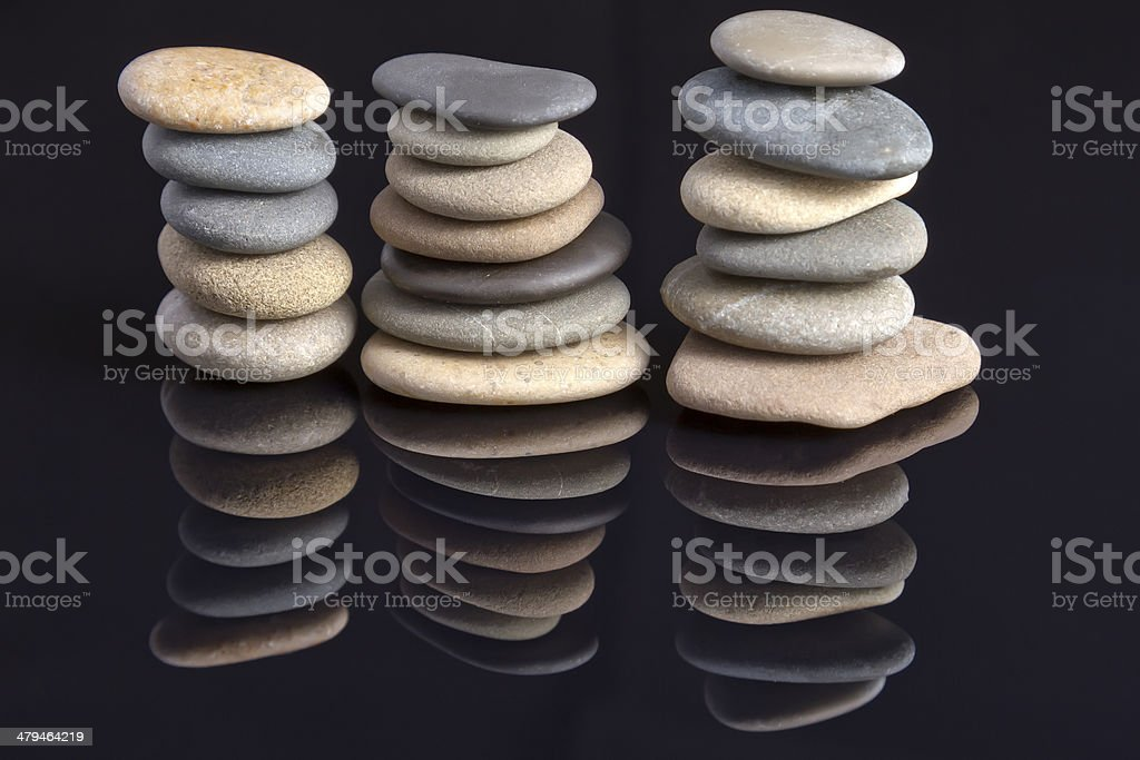 Sea stones laid in piles reflected off the black stock photo