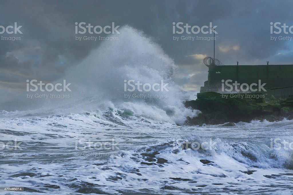Sea storm waves crashing and splashing against pier stock photo
