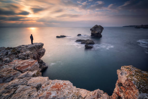 Sea sunrise at rocky beach Magnificent sea sunrise at the rocky Black sea coast with a lone rock in the sea and a silhouette of a man rocky coastline stock pictures, royalty-free photos & images