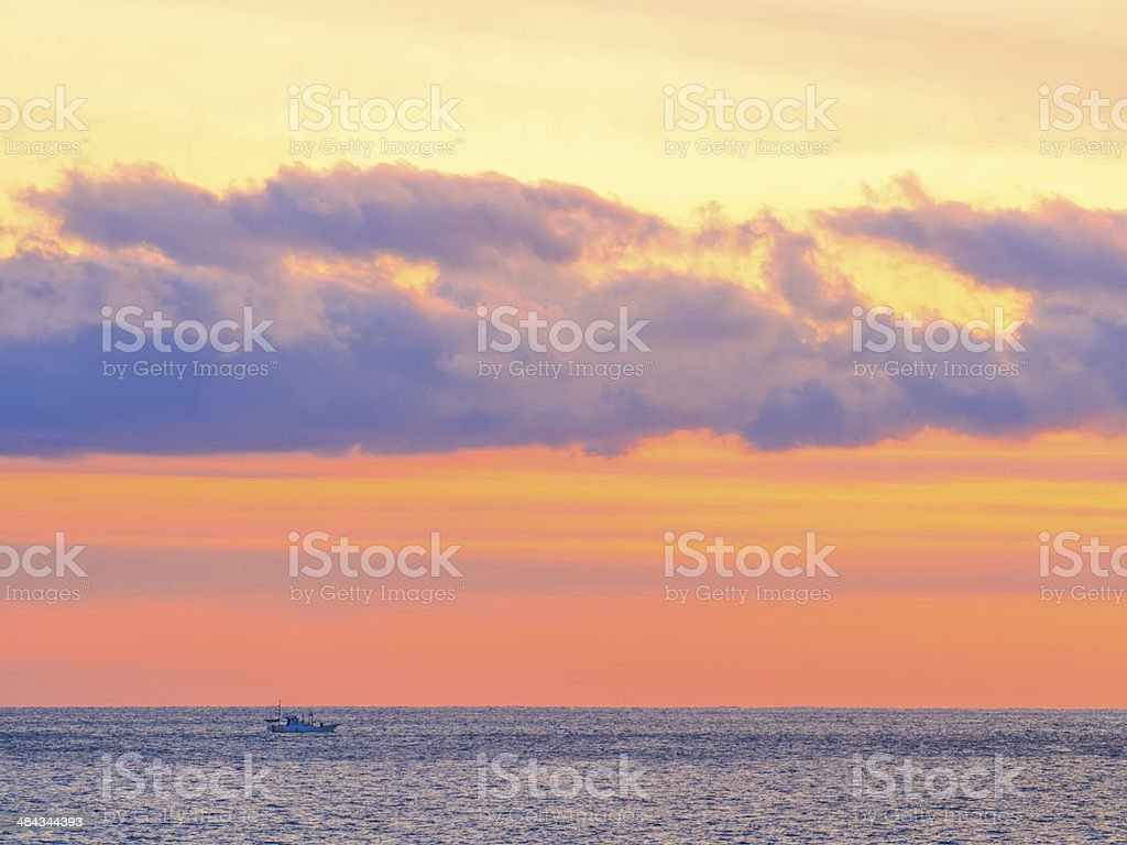 Sea sunset glow with clouds and sailing fishing boat royalty-free stock photo