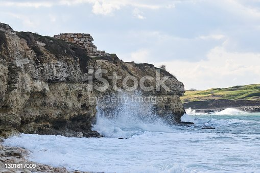 sea surf destroys a coastal cliff with the ruins of an ancient building on it