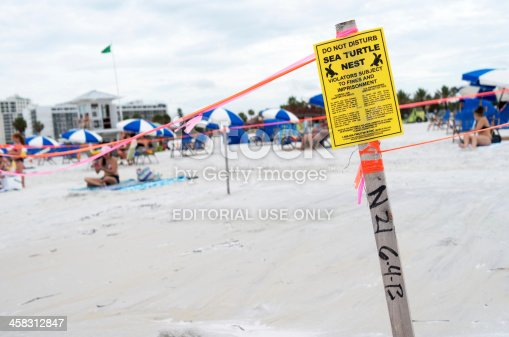 Clearwater, Florida USA - July 3, 2013. A sea turtle nesting site on Clearwater beach is taped off with caution tape and Warning signs.  The nesting site is in the middle of a very  busy beach.