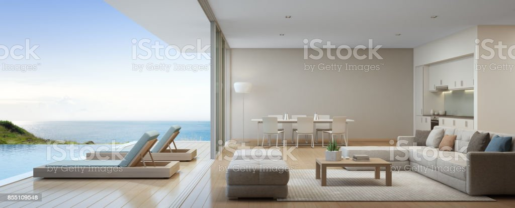 Sea view kitchen, dining and living room of luxury beach house with terrace near swimming pool in modern design. Vacation home or holiday villa for big family. stock photo