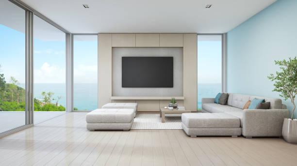 meer blick wohnzimmer luxus strandhaus mit glastür und holzterrasse. großen weißen sofa gegen blaue wand in der nähe von tv im hause oder im urlaub ferienhaus für großfamilie. - küstenfamilienzimmer stock-fotos und bilder