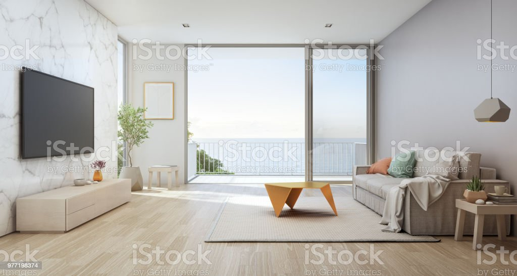 Sea view living room of luxury beach house with glass door and wooden terrace. TV on white marble wall against sofa near indoor plant in vacation home or holiday villa. stock photo