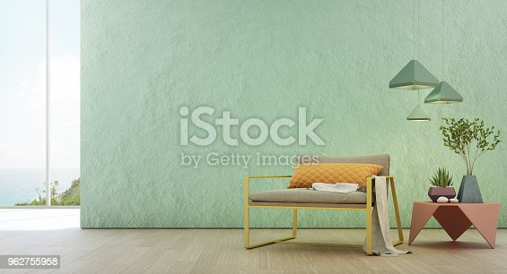 istock Sea view living room of luxury summer beach house with glass window and wooden floor. Empty rough turquoise concrete wall background in vacation home or holiday villa. 962755958