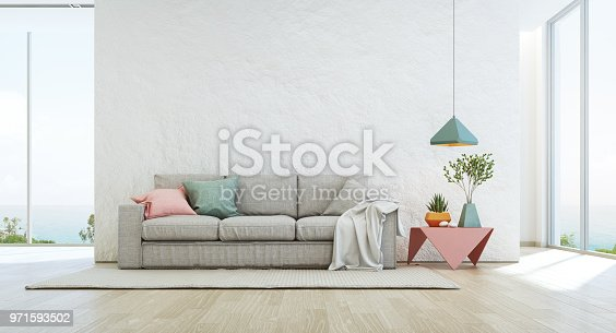 istock Sea view living room of luxury summer beach house with glass window and wooden floor. Empty rough white concrete wall background in vacation home or holiday villa. 971593502