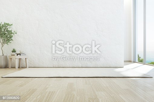 istock Sea view living room of luxury summer beach house with glass window and wooden floor. Empty rough white concrete wall background in vacation home or holiday villa. 972550520